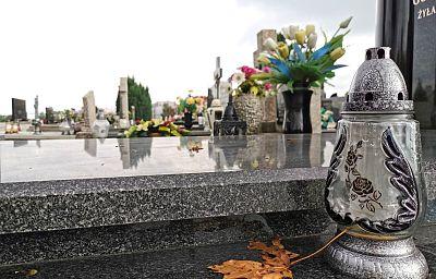 Nagrobek granitowy na cmentarzu. Na pierwszym planie stoi na nim szklany znicz, obok leży żółty liść klonu. W tle stoją kwiaty sztuczne w wazonie, dalej kolejne nagrobki.
