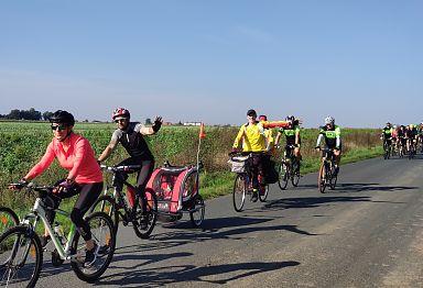 Droga asfaltowa, po której jedzie peleton cyklistów