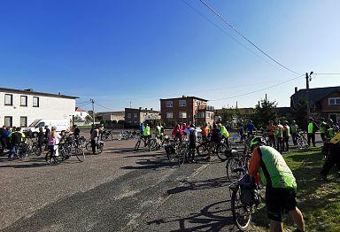 Asfaltowy plac pomiędzy zabudowaniami, zapełniony rowerzystami