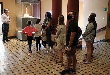 w holu trzeciego piętra, przed drzwiami do wieży, stoi grupa zwiedzających i przewodnik