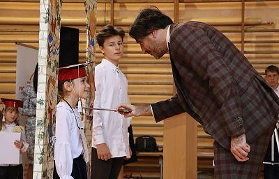 Wiceprezydent Grzegorz Kulawinek dokonuje pasowania na ucznia dziewczynki ubranej w białą bluzkę