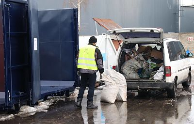 Ubrany w odblaskową kamizelkę pracownik Punktu Selektywnej Zbiórki  Odpadów Komunalnych rozładowuje worki z odpadami z otwartego bagażnika białego samochodu. Po lewej stronie niebieski kontener na odpadu.