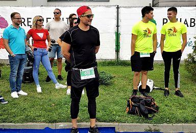 Na zdjęciu prezydent Krystian Kinastowski, który obserwuje zaowody Calisia Triathlon. W tle inni uczestnicy wydarzenia